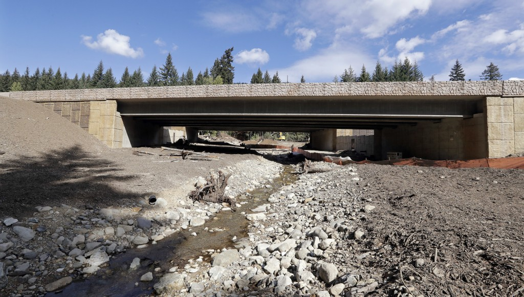 In this photo taken Oct. 4, 2018, high walls block the view of traffic on Interstate 90 above a wildlife passage and creek bed below and near a wildli...