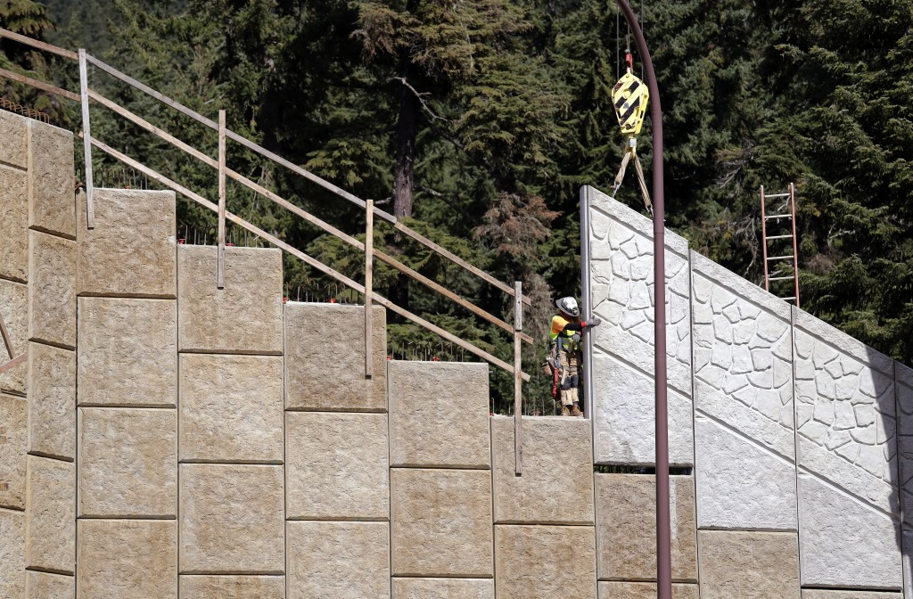 In this photo taken Oct. 4, 2018, a worker helps install tall panels on a wildlife bridge under construction over Interstate 90 on Snoqualmie Pass, Wa...