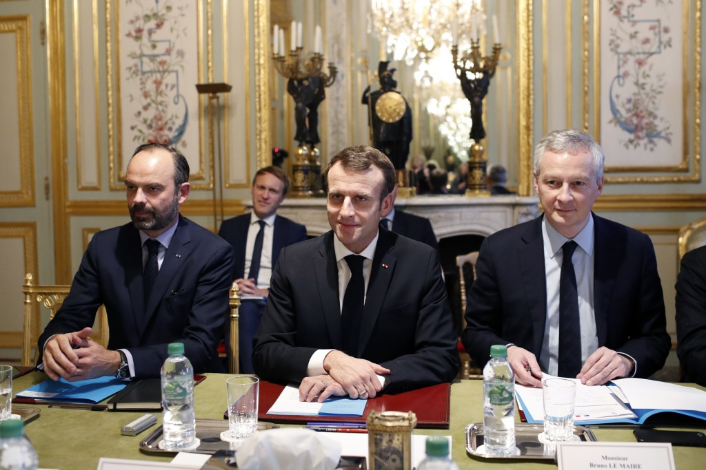 France's President Emmanuel Macron, center, France's Prime Minister Edouard Philippe, left, and France's Finance Minister Bruno Le Maire, right, atten...