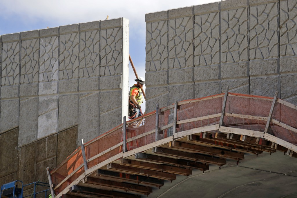 In this photo taken Oct. 4, 2018, a worker walks past a gap where tall panels are being erected on a wildlife bridge under construction over Interstat...