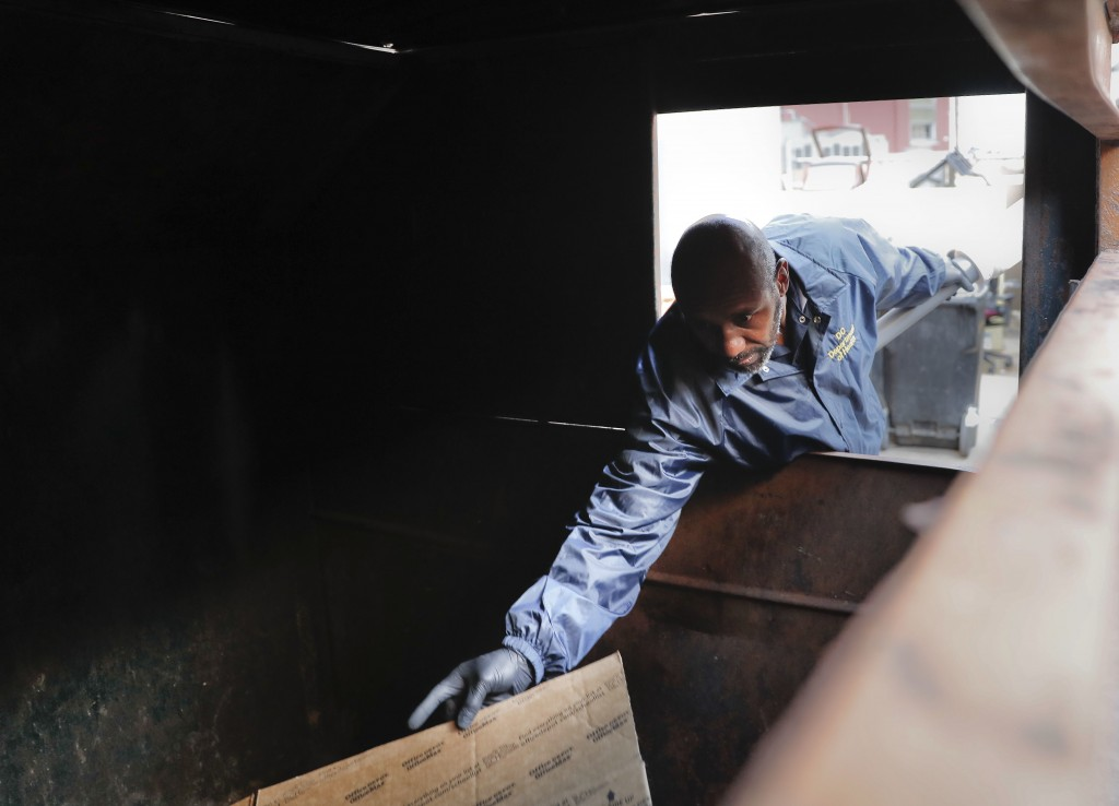 Pest Control Officer Gregory Cornes, from the D.C. Department of Health's Rodent Control Division, inspects a trash dumpster in an alley behind an off