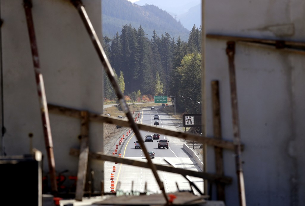 In this photo taken Oct. 4, 2018, Interstate 90 traffic passing beneath a wildlife bridge under construction is seen through a gap where tall panels a...