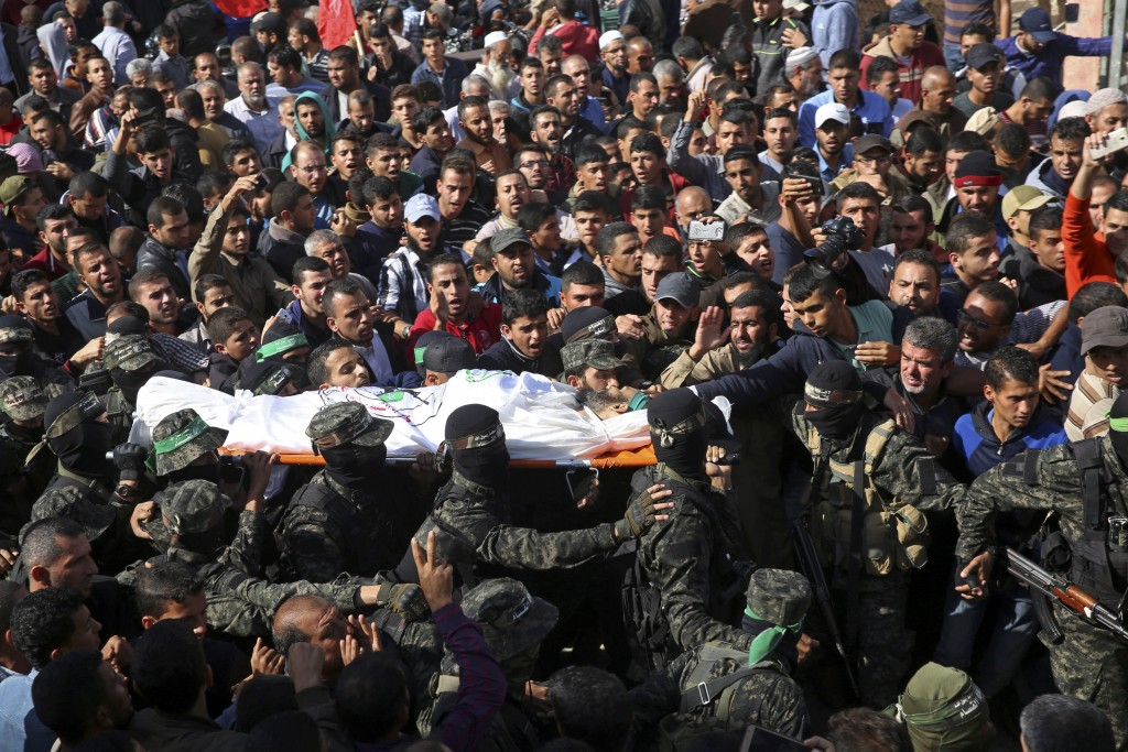 FILE - In this Monday, Nov. 12, 2018 file photo, mourners carry the body of Hamas militant commander Nour Baraka, who was killed during an Israeli rai