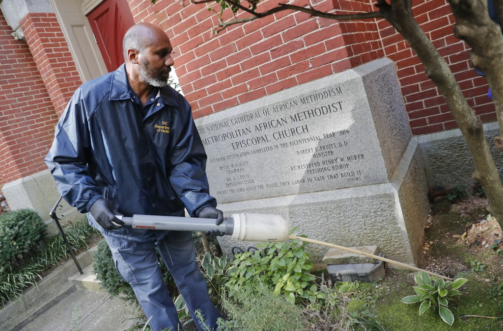 Pest Control Officer Gregory Cornes, from the D.C. Department of Health's Rodent Control Division, uses a duster to pump poison into rat burrows, foun