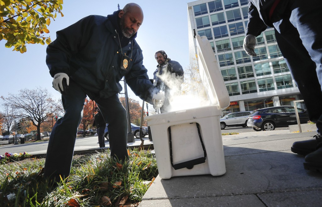 Pest Control Officers Gregory Cornes, left, uses a hand trowel to scoop-up dry ice before dropping it directly into rat burrows, as his co-worker Curt