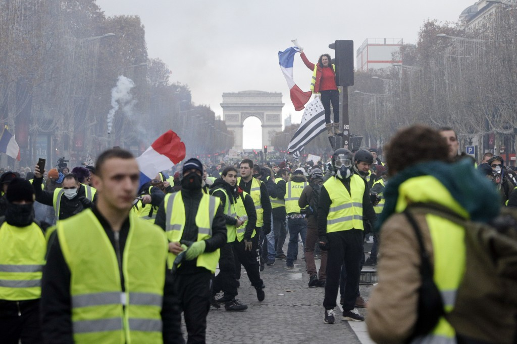 FILE - In this Nov. 24, 2018, file photo, demonstrators march on the famed Champs-Elysees avenue in Paris, France, as they protest the rising of the f