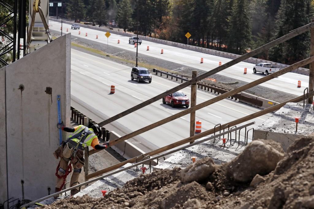 In this photo taken Oct. 4, 2018, a worker helps place tall panels on a wildlife bridge under construction as traffic on Interstate 90 passes below on...