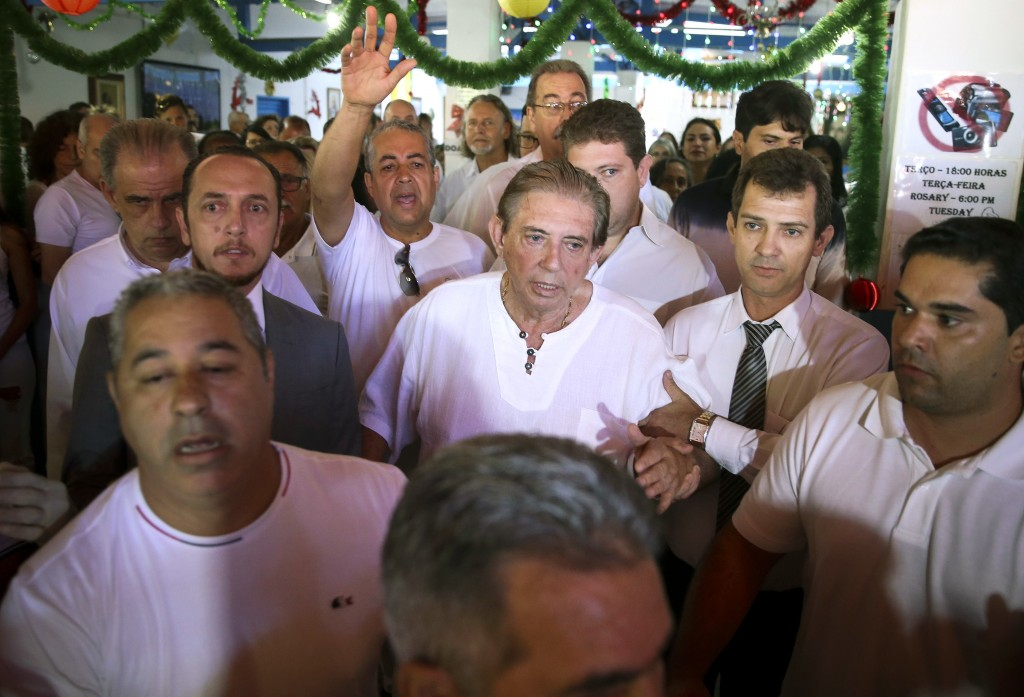 In this handout photo released by Agencia Brasil, spiritual healer Joao Teixeira de Faria, better known as John of God, center, arrives to the Dom Ina