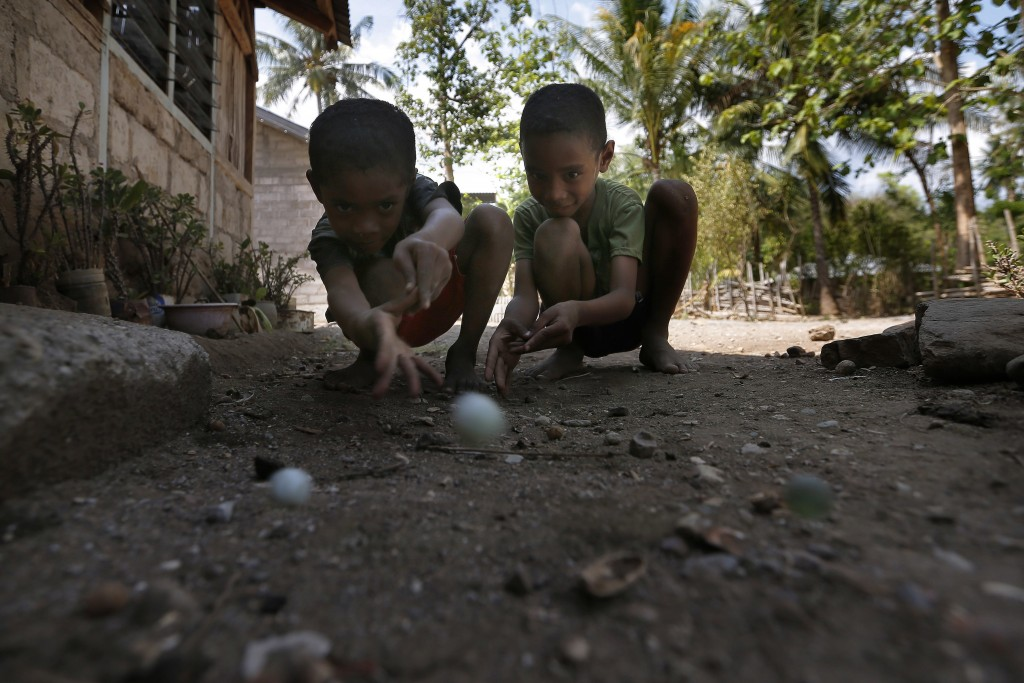 In this Oct. 22, 2018, photo, two boys play a game of marbles in Fatukoko village, West Timor, Indonesia. Children in this impoverished region of Indo...