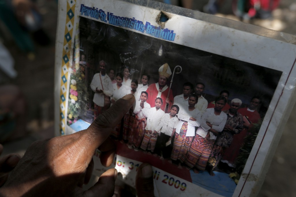 In this Oct. 23, 2018, photo, Laurencius Kollo holds up a photograph taken in July 2009, which shows Marselina Neonbota, (third from left) posing with