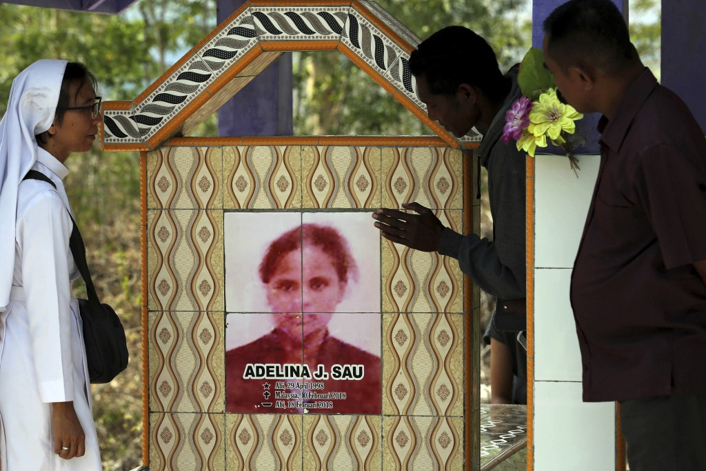 In this Oct. 21, 2018, photo, Sister Laurentina, left, stands next to the tombstone of Adelina Sau in Abi village in West Timor, Indonesia. Adelina di