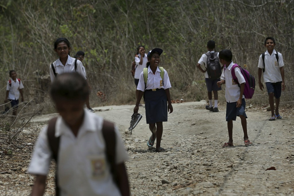 In this Oct. 22, 2018, file photo, students walk on dirt road after school in O'of village in West Timor, Indonesia. Children in this impoverished reg