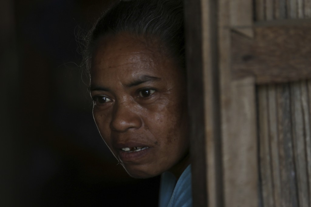 In this Oct. 22, 2018, photo, Margarita Oematan, grandmother of Orance Faot, looks out of her home in O'of Village in West Timor, Indonesia. Orance's