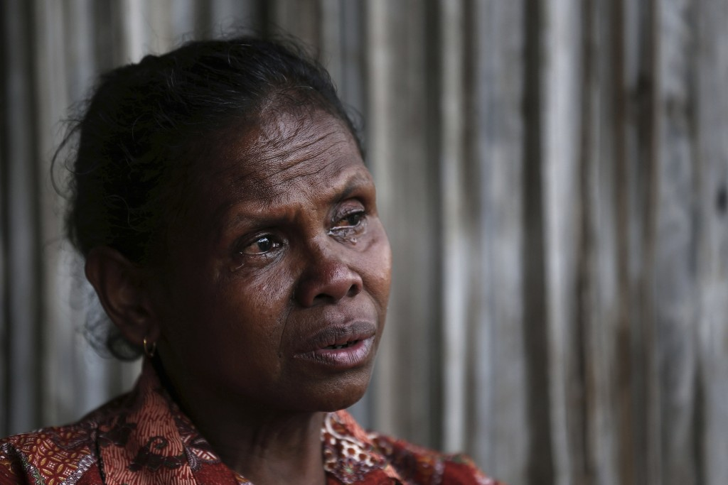 In this Oct. 21, 2018, photo, Yohanna Banunaek, cries as she talks about her late daughter Adelina Sau, in Abi village in West Timor, Indonesia. Sau h...