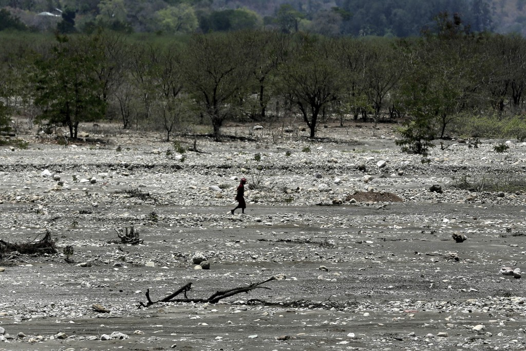 In this Oct. 23, 2018, photo, a man walks across a dry river bed in Fatukoko village in West Timor, Indonesia. The region is one of the driest parts o