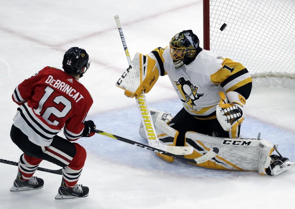 Chicago Blackhawks left wing Alex DeBrincat, left, scores against Pittsburgh Penguins goalie Casey DeSmith during the second period of an NHL hockey g...