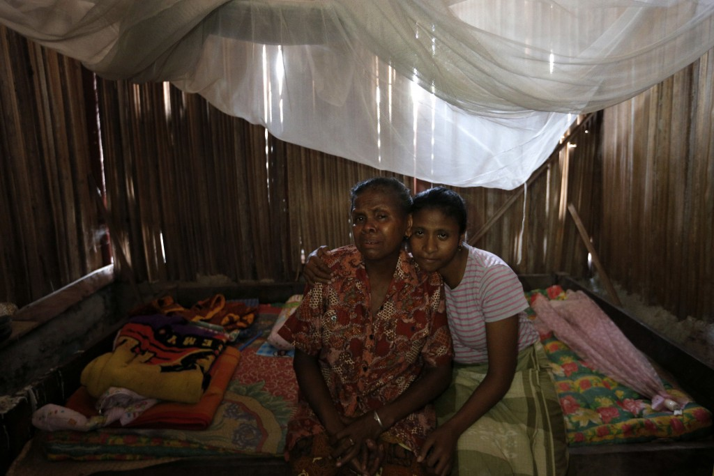 In this Oct. 21, 2018, photo, Yohanna Banunaek, left, is comforted by her daughter Yeti, in Abi village in West Timor, Indonesia, while they grieve th