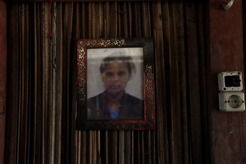 In this Oct. 21, 2018, photo, a framed photo of Adelina Sau hangs on the wall of her family's home in Abi village in West Timor, Indonesia. Adelina ha...