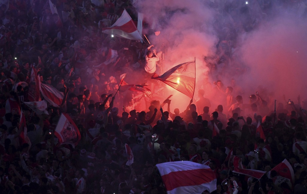 River Plate soccer fans celebrate with flags and flares their team's 3-1 victory over Boca Juniors and clenching the Copa Libertadores championship ti