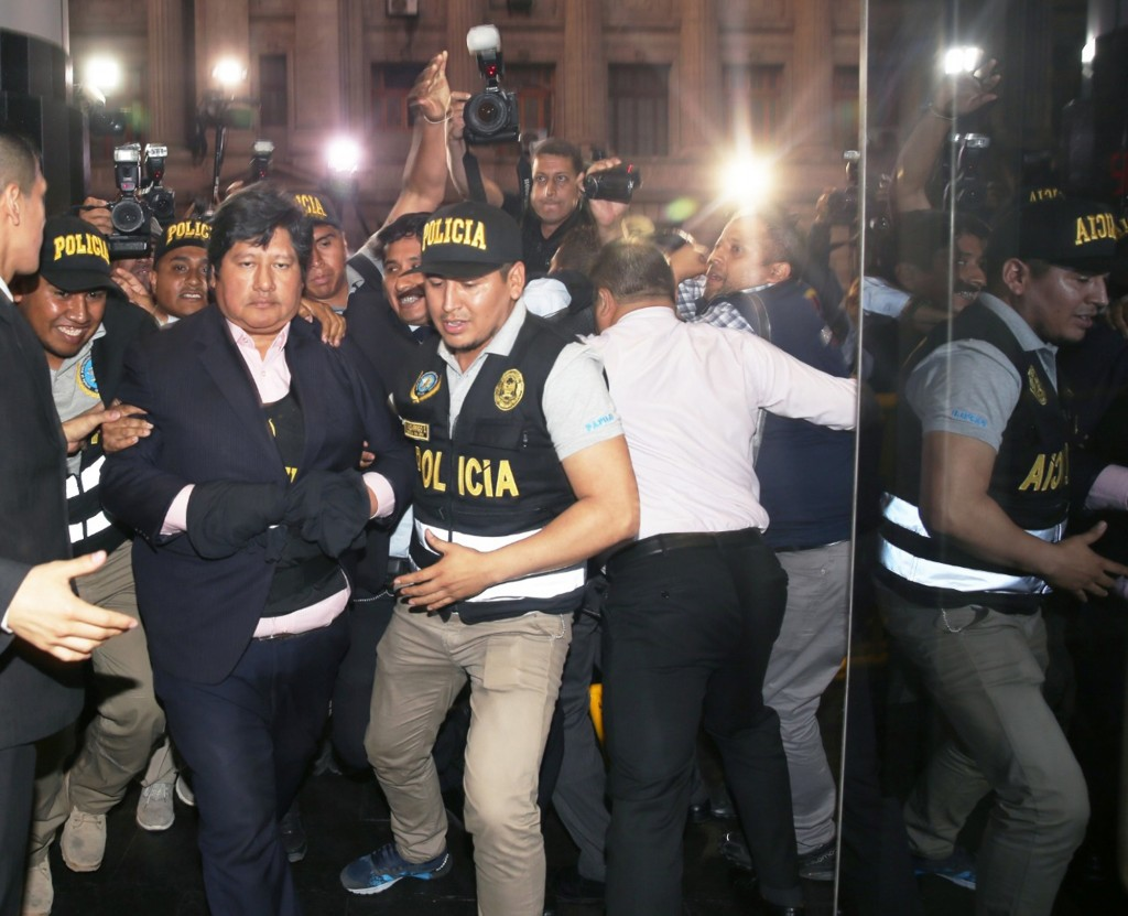 In this photo provided by Peru's Justice Palace press office, Peru's Football Federation President Edwin Oviedo is lead to jail in handcuffs in Lima,
