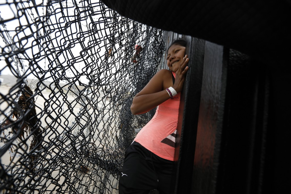 A Honduran migrant, followed by her daughter, squeezes through a gap in the U.S. border wall from Tijuana, Mexico, onto U.S. soil near Imperial Beach,