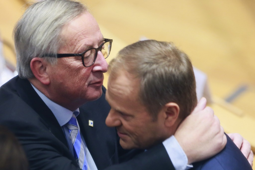 European Commission President Jean-Claude Juncker, left, embraces European Council President Donald Tusk during a round table meeting at an EU summit ...