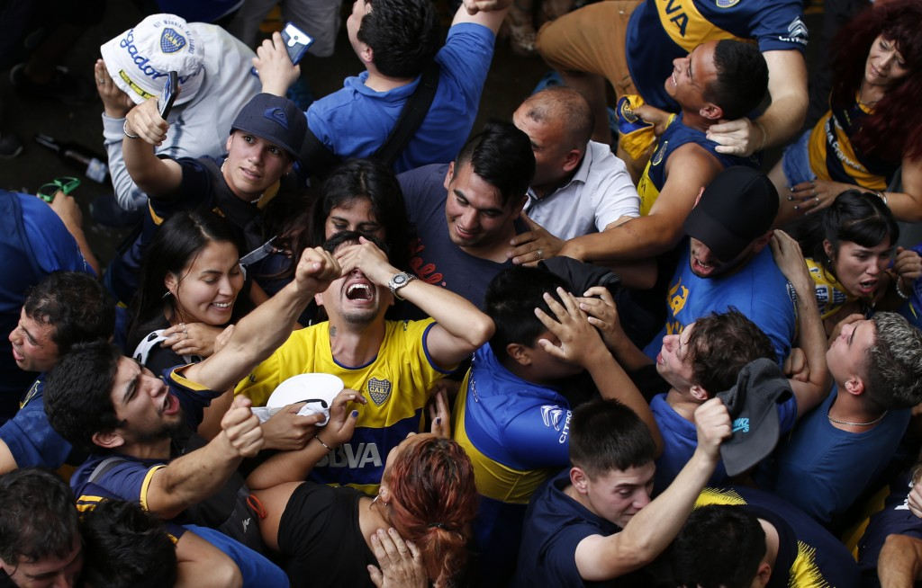 Boca Juniors soccer fans celebrate their team's goal as they watch on TV the Copa Libertadores final against River Plate in Buenos Aires, Argentina, S