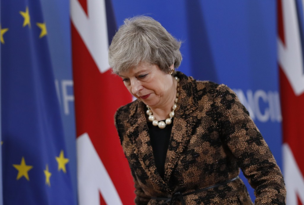 British Prime Minister Theresa May walks by the Union Flag and EU flag as she departs a media conference at an EU summit in Brussels, Friday, Dec. 14,...