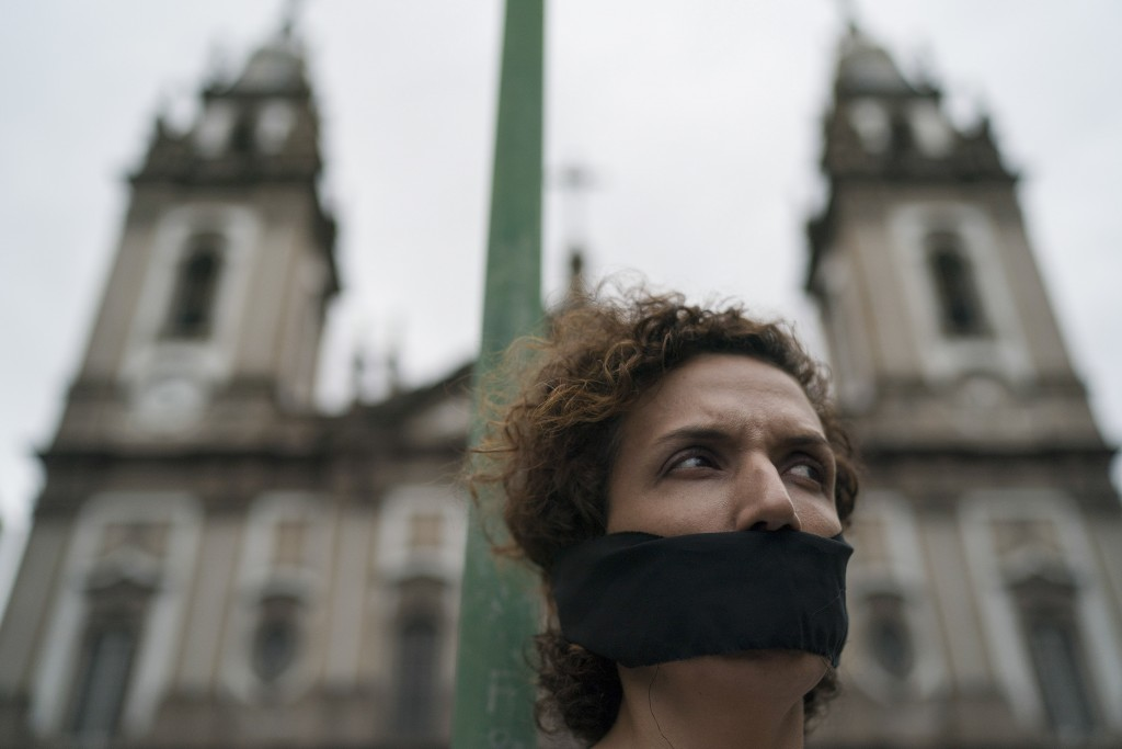 A woman wears a gag over her mouth during an event to remember the victims of Brazil's dictatorship, in downtown Rio de Janeiro, Brazil, Saturday, Dec