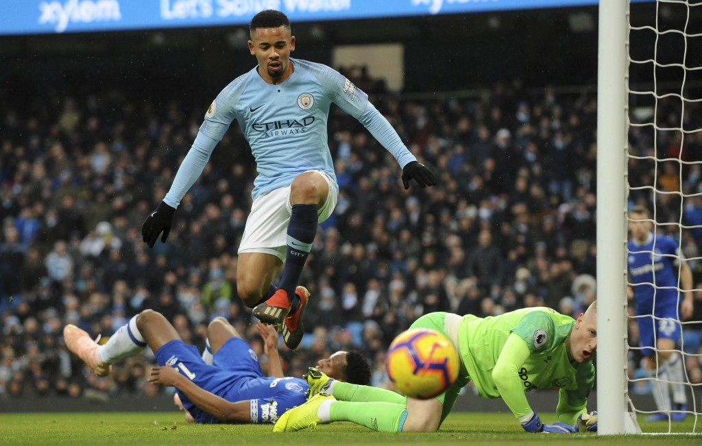 Manchester City's Gabriel Jesus, center, jumps over Everton's Jordan Pickford, right, during the English Premier League soccer match between Mancheste...
