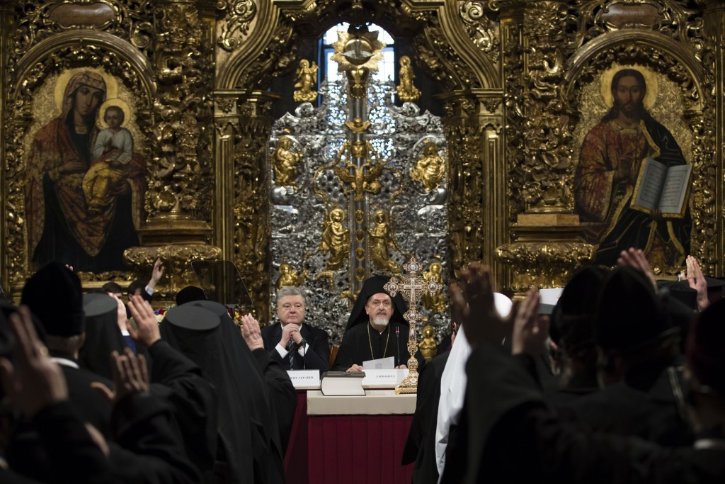 Ukrainian President Petro Poroshenko, center left, attends a closed-door synod of three Ukrainian Orthodox churches to approve the charter for a unifi...