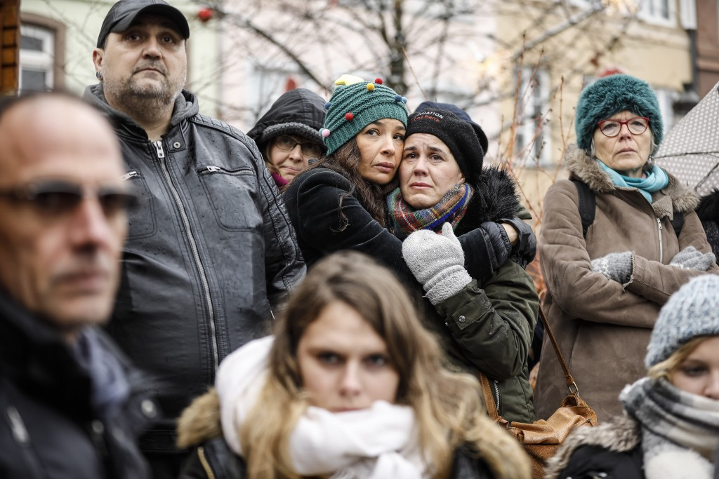 Residents react during a gathering being held in a central square of the eastern French city of Strasbourg, Sunday Dec.16, 2018 to pay homage to the v...