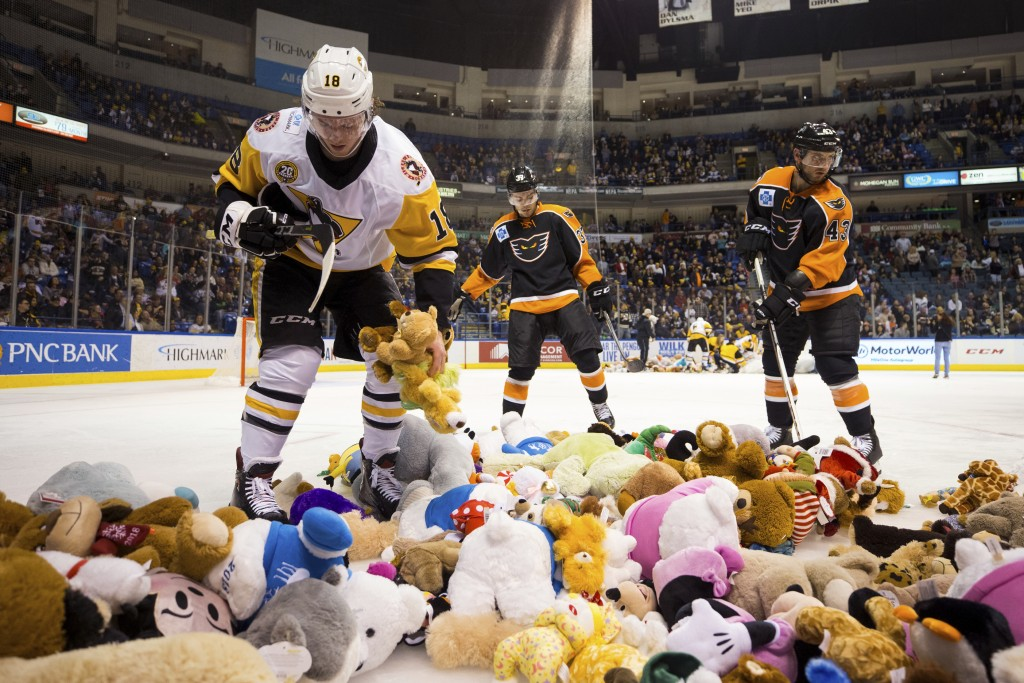 The Wilkes-Barre/Scranton Penguins' Sam Lafferty, left, cleans up teddy bears thrown on the ice with help from Lehigh Valley Phantoms players Mark Fri...