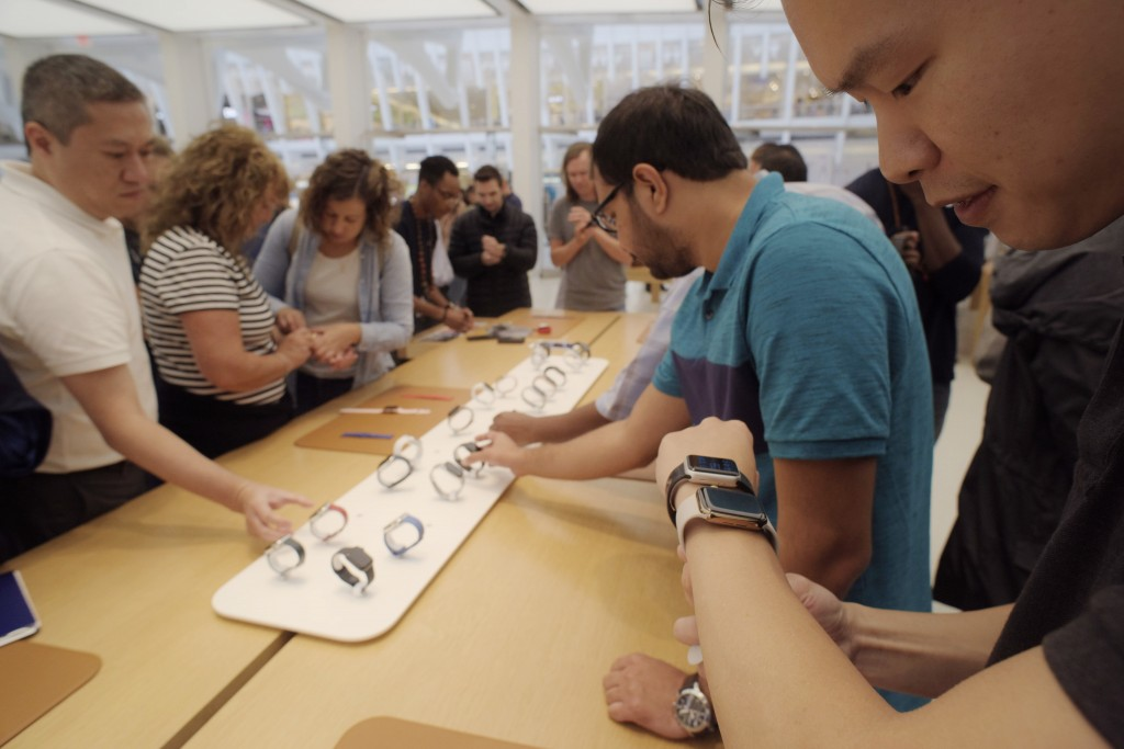 FILE- In this Sept. 21, 2018, file photo customers look at new Apple watches including the Series 4 at an Apple store in New York. The new Apple Watch