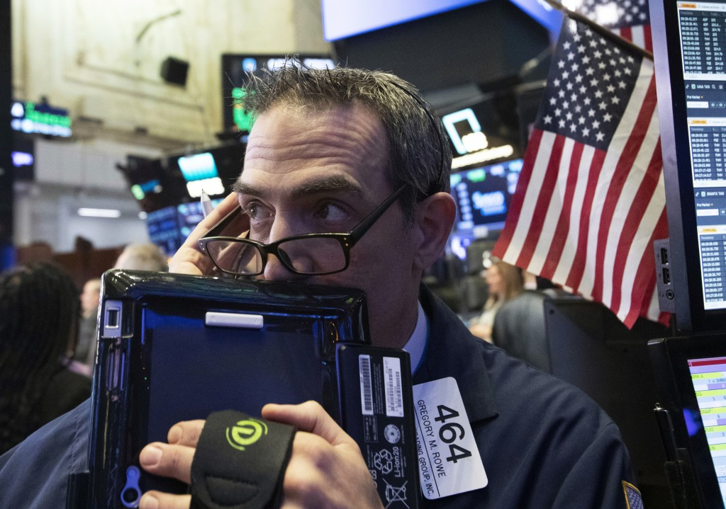 FILE- In this Dec. 12, 2018, file photo trader Gregory Rowe works at the New York Stock Exchange in New York. The U.S. stock market opens at 9:30 a.m....
