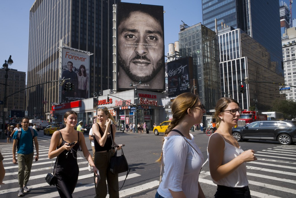 """FILE - In this Sept. 6, 2018 file photo, people walk by a Nike advertisement featuring Colin Kaepernick in New York. In his """"Just Do It"""" spot for Nike..."""