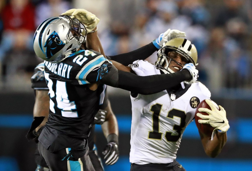 New Orleans Saints' Michael Thomas (13) and Carolina Panthers' James Bradberry (24) grab each other's face masks in the second half of an NFL football