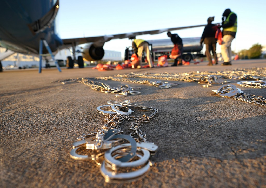 In this Friday, Nov. 16, 2018, photo, restraints lie on the tarmac as personal belongings of immigrants who entered the United States illegally are lo...