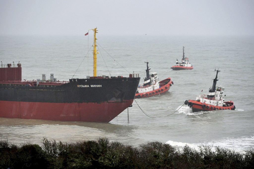 Tugs manoeuvre the Kuzma Minin, a 16,000-tonne Russian cargo ship, as attempts are made to refloat it after it ran aground off Gyllyngvase Beach in Fa