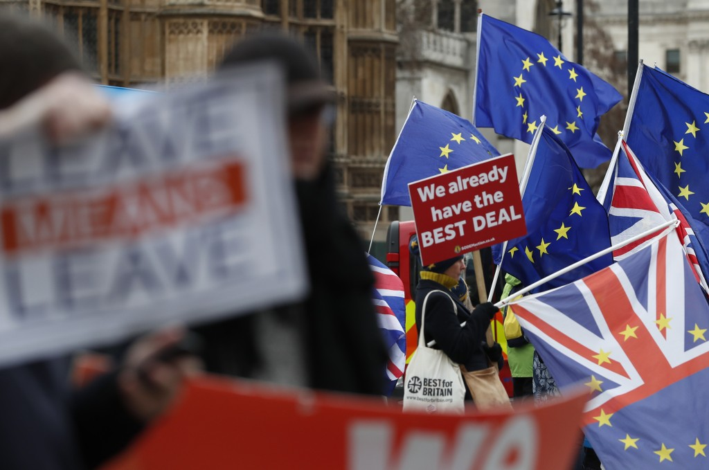 Pro and anti Brexit demonstrators wave their placards and flags outside the Houses of Parliament in London, Tuesday Dec. 18, 2018. The British Cabinet