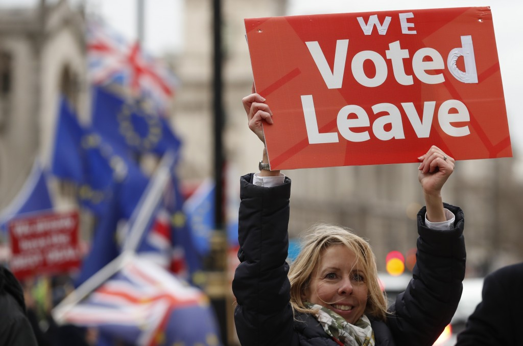A pro-Brexit demonstrator waves a placard with others outside the Houses of Parliament in London Tuesday, Dec. 18, 2018. The British Cabinet was meeti