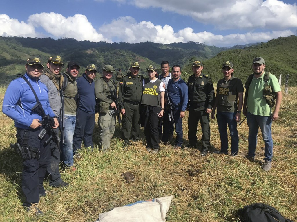 In this handout photo released by the press office of Colombia's National Police, Melissa Martinez Garcia poses for a photo with the officers that res...