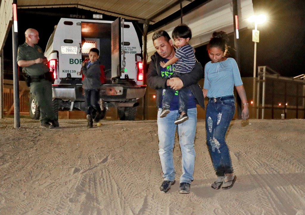 FILE - In this July 18, 2018 file photo, a Honduran man carries his 3-year-old son as his daughter and other son follow to a transport vehicle after b