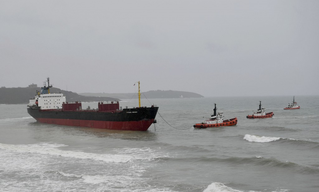 Tugs manoeuvre the Kuzma Minin, a 16,000-tonne Russian cargo ship, as attempts are made to refloat it after it ran aground off Gyllyngvase Beach in Fa...