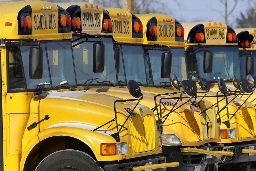 FILE - This Jan. 7, 2015 file photo shows public school buses parked in Springfield, Ill. Child abuse increases the day after school report cards are ...