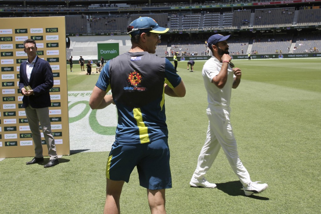 Australian captain Tim Paine, center, and his India counterpart Virat Kohli walk past each other without acknowledgement during the post match intervi...