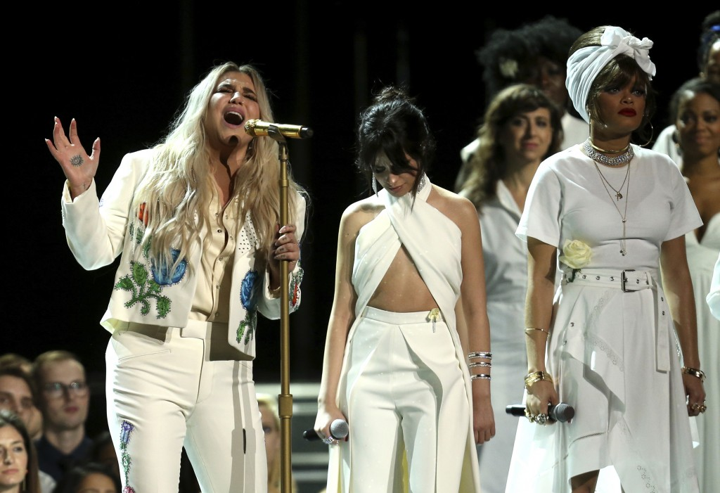 "FILE - In this Jan. 28, 2018 file photo, Kesha, left, performs ""Praying"" as Camila Cabello, center, and Andra Day stand by at the 60th annual Grammy A"
