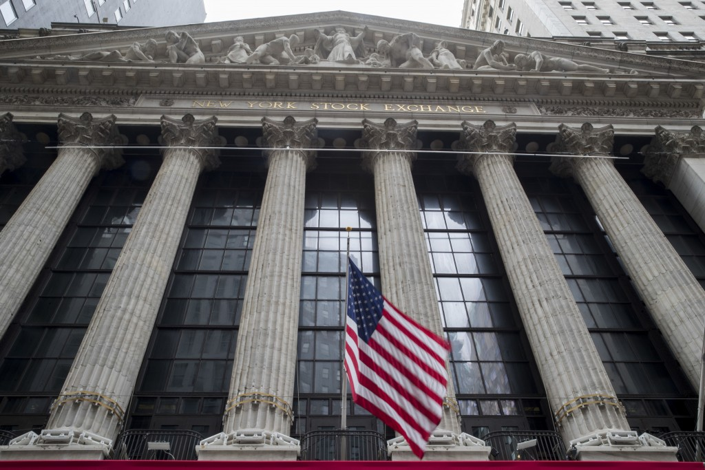 FILE - In this Nov. 20, 2018, file photo an American flag flies outside New York Stock Exchange. Stocks are opening solidly higher on Wall Street as t...