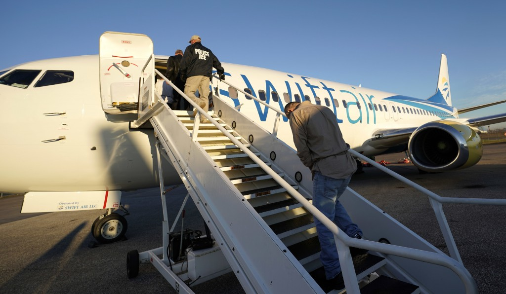 In this Nov. 16, 2018, photo, immigrants who entered the United States illegally are deported on a flight to El Salvador by U.S. Immigration and Custo...