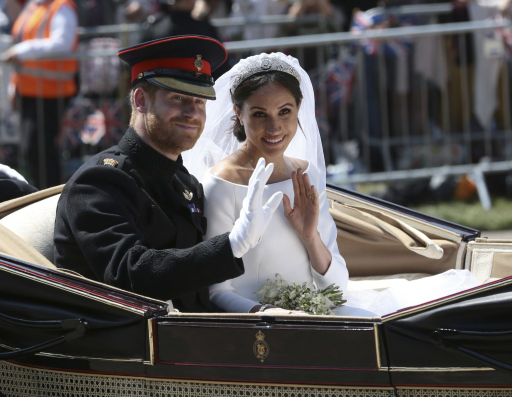 FILE - In this May 19, 2018 file photo, Britain's Prince Harry and Meghan Markle ride in an open-topped carriage after their wedding ceremony at St. G